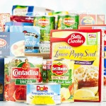 """""""Suffolk, Virginia, USA - August 16, 2012: A horizontal studio shot of an assortment of non-perishable food items purchased from American grocery stores. Items include, canned goods from Del Monte, Contadina, Green Giant and Dole, and packaged goods from Nabisco, Knorr, Crown Prince, Kraft, Success, Barilla, Betty Crocker and Minute. The groceries in the background are in a cardboard box."""""""
